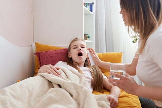Mãe usando spray médico para filha em casa, dor de garganta