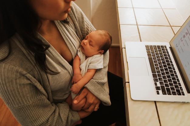 Mãe, usando, um, computador, e, segurando, dela, bebê
