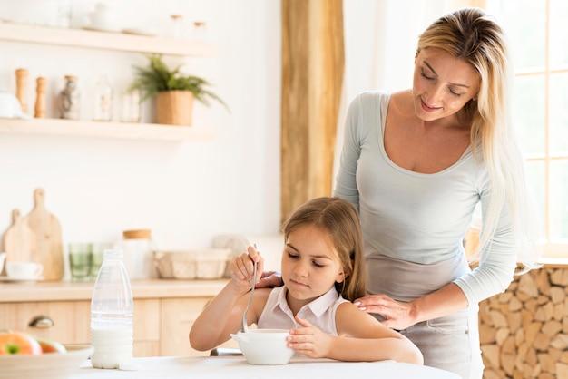 Mãe vendo sua filha tomar café da manhã