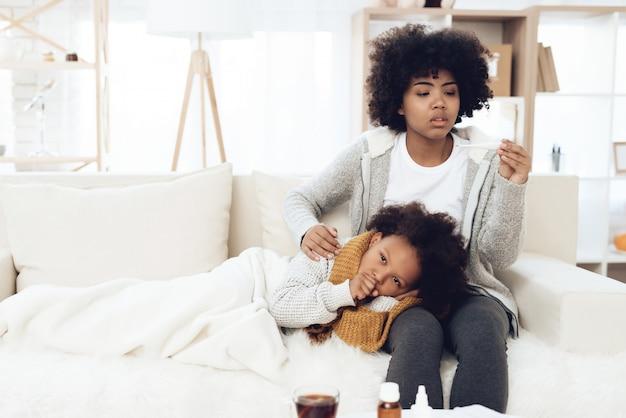 Mãe verifica a temperatura do garoto doente com gripe.