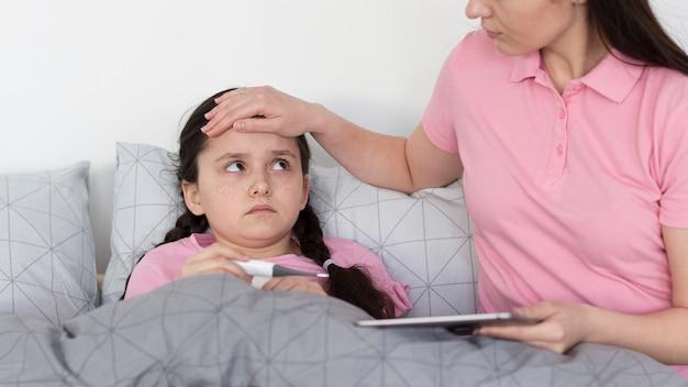 Mãe, verificando a febre da menina