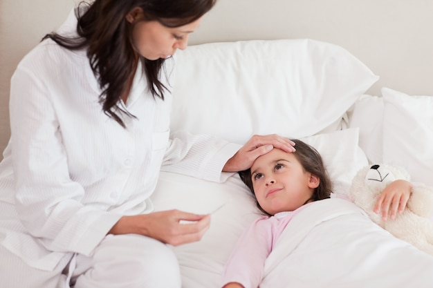Mãe verificando a temperatura da filha