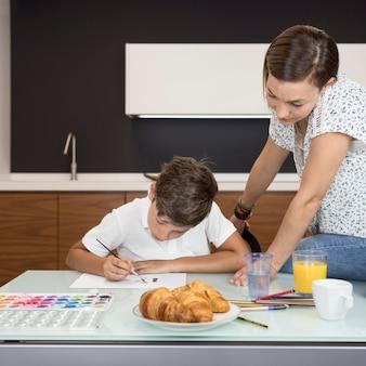 Mãe verificando filhos pintando em casa