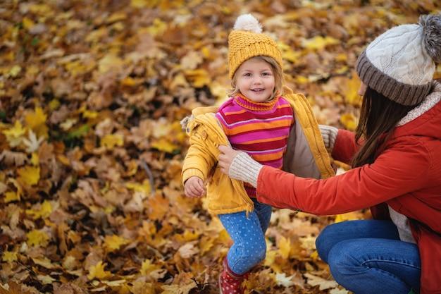 Mãe veste a jaqueta da filha pequena na floresta de outono