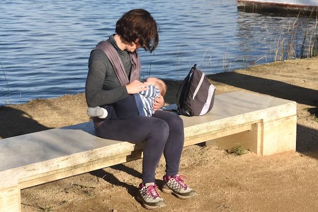 Mãe vestida com roupa esportiva amamentando seu filho