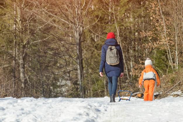 Mãe withlittle filho caminhando ao longo da neve