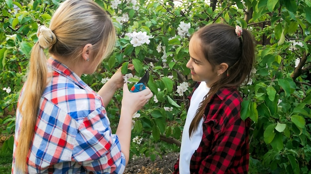 Mãe yougn ensinando adolescente a cortar galhos e cuidar do jardim.