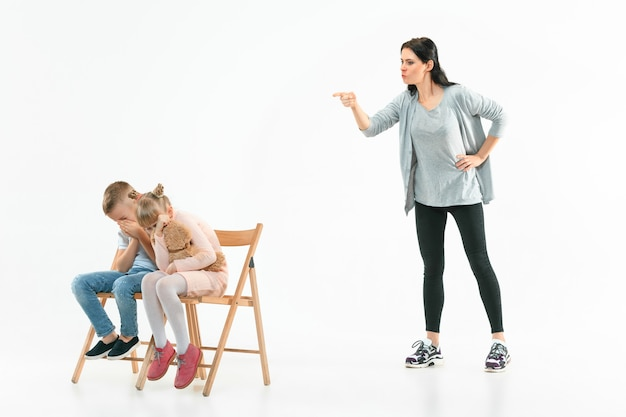 Mãe zangada repreendendo filho e filha em casa