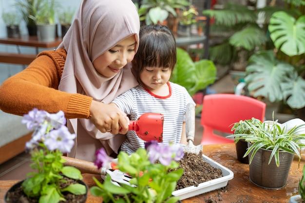 Mães asiáticas veladas ajudam suas filhas a segurar pequenas pás para tirar o solo das bandejas