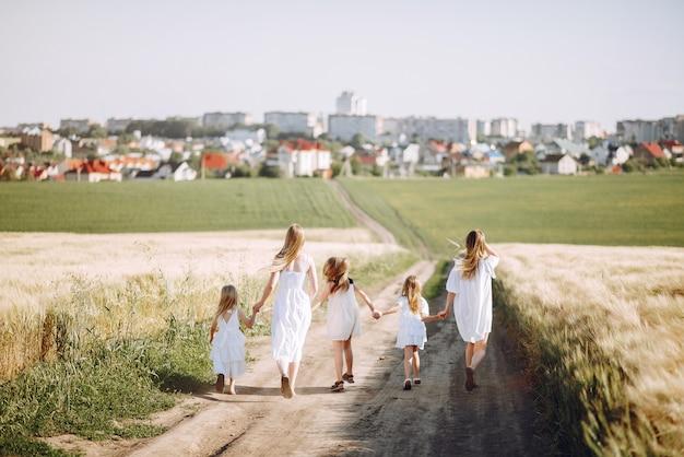 Mães com filhas brincando em um campo de outono