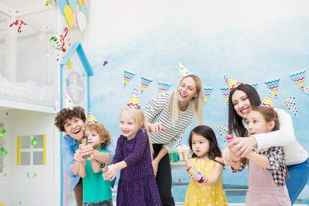 Mães e crianças em êxtase estourando biscoitos Foto Premium
