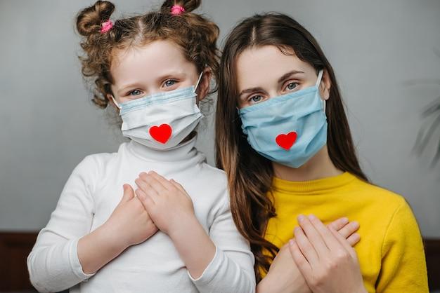 Mães e filha de mãos dadas no peito sentam-se na cama, usam máscara facial com o coração, como forma de agradecer aos médicos e enfermeiras pela ajuda na luta contra a doença. covid-19