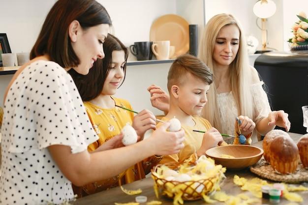 Mães e filhos pintando ovos de páscoa.