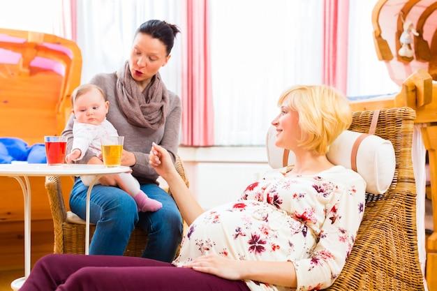 Mães felizes falando sobre gravidez no consultório de parteira