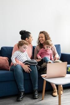 Mães lgbt em casa com filhos no sofá