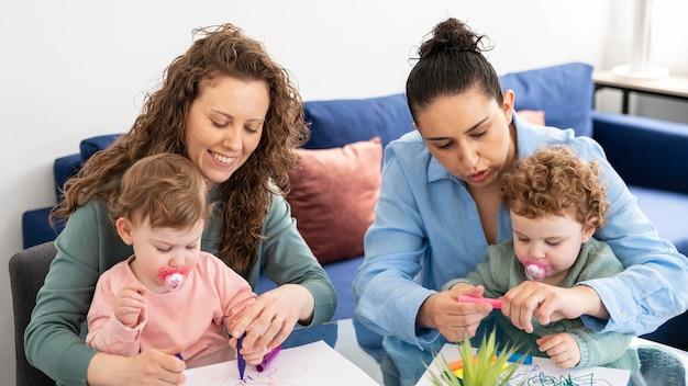 Mães lgbt em casa desenhando com seus filhos