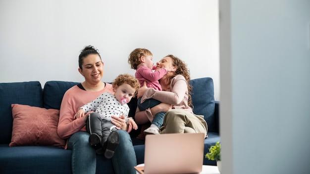 Mães lgbt em casa no sofá com os filhos