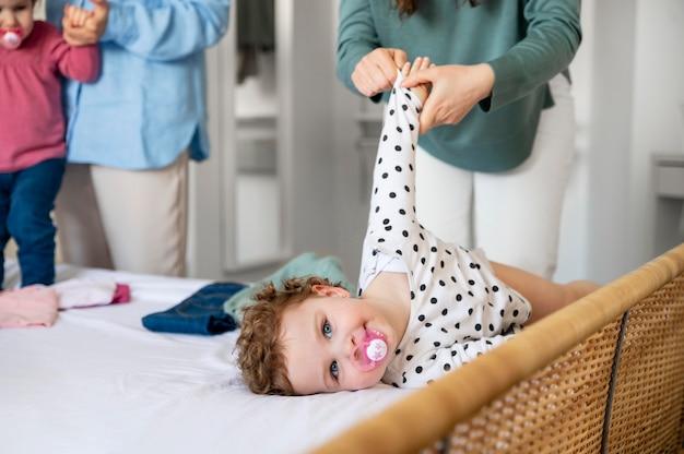 Mães lgbt em casa trocando a roupa dos filhos