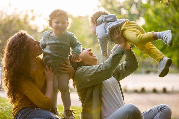 Mães lgbt felizes ao ar livre no parque com seus filhos