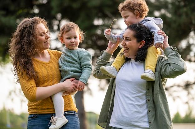 Mães lgbt felizes lá fora no parque com seus filhos