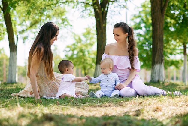 Mães na moda elegantes jovens senta-se com suas filhas na grama em um parque.