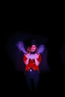 Mágica faz show com bolhas de sabão e fumaça, uma ilusionista com roupas teatrais, na parede preta. atriz mulher com fantasia de palco e cartola na cabeça. conceito de desempenho. copie o espaço