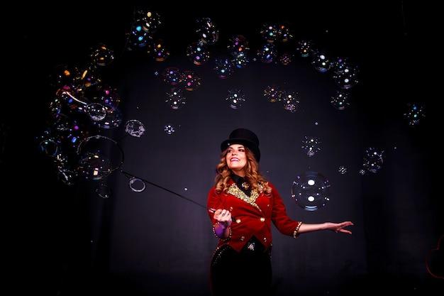 Mágica feminina faz show com bolhas de sabão, uma ilusionista com roupas teatrais, sobre fundo preto. atriz mulher com fantasia de palco e cartola na cabeça. conceito de desempenho. copie o espaço