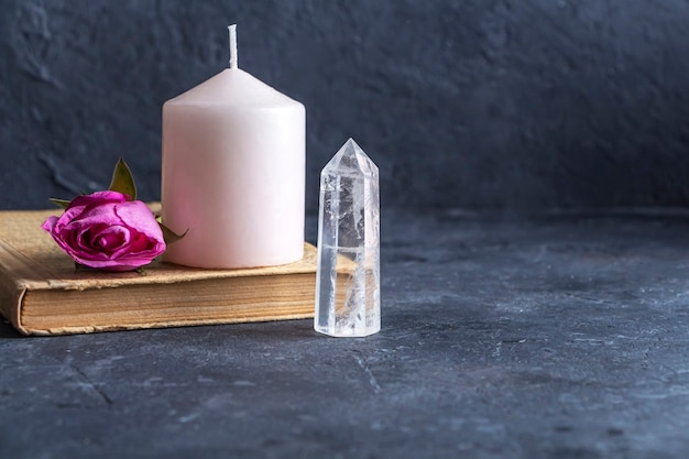 Mágica natureza morta vintage com cristais, vela rosa, livro antigo e flores rosas.