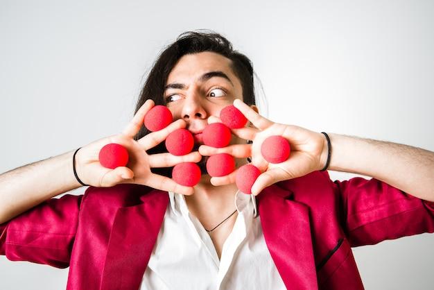 Mágico com bolas vermelhas nas mãos estendidas.
