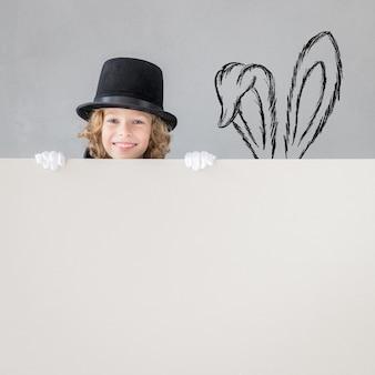Mágico criança se escondendo atrás de um cartaz em branco.