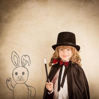 Mágico criança segurando a varinha. conceito de sucesso