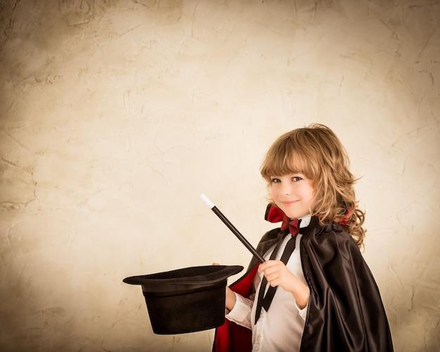 Mágico criança segurando cartola e varinha mágica. conceito de sucesso