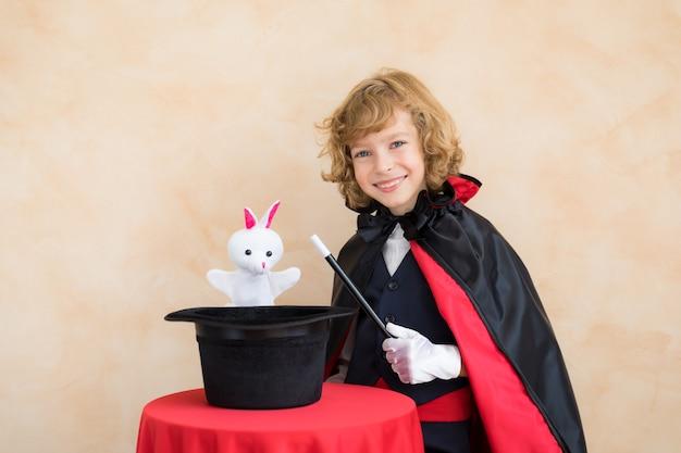 Mágico criança segurando uma cartola com coelho de brinquedo. em casa