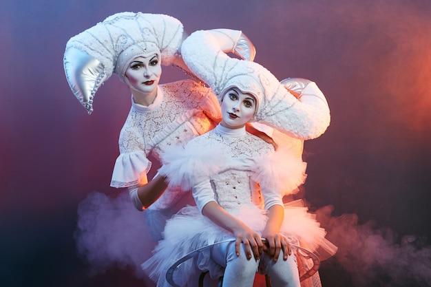 Mágico de artista de circo mostra truques com bolhas de sabão. uma mulher e uma garota inflam bolhas de sabão