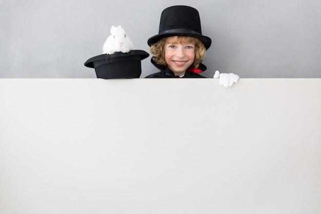Mágico infantil com coelho se escondendo atrás de um cartaz em branco.