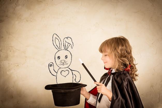 Mágico infantil segurando uma cartola com um coelho desenhado contra o fundo do grunge. concentre-se no chapéu