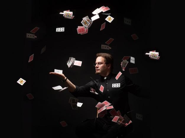 Mágico joga cartas no ar.
