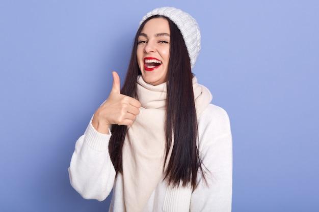 Magnética emocional fêmea bonita rindo, tendo emoções positivas, levantando o polegar, fazendo o gesto