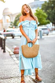 Magnífica jovem blogueira elegante e positiva posando na rua usando um vestido da moda feminina e uma bolsa de palha em cores suaves e ensolaradas.