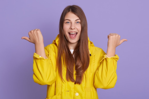 Magnífica mulher adorável bonita e encantadora, com cabelos longos na camisa amarela casual, apontando de lado com as duas mãos, isolado sobre a parede lilás.