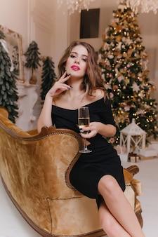 Magnífica mulher branca com rosto inspirado bebe champanhe durante a celebração do ano novo. garota atraente em um vestido preto relaxando no sofá na festa de natal.