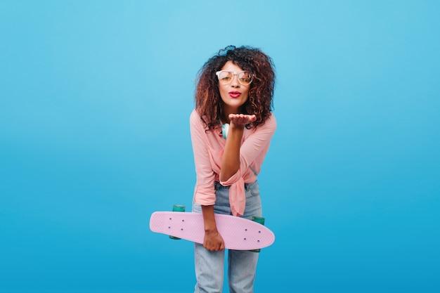 Magnífica mulher negra em camisa de algodão rosa mandando beijo no ar. retrato interior de modelo feminino muito mulata com longboard posando com expressão de rosto adorável.