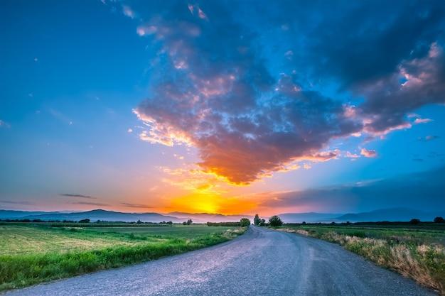 Magnífica paisagem de uma estrada em um prado no fundo de um lindo céu do sol com nuvens