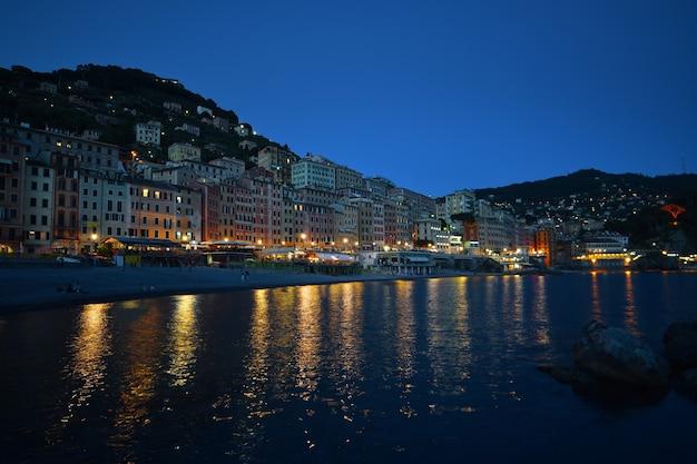 Magnífica vista noturna da cidade de camogli com luzes, cores e reflexos no mar