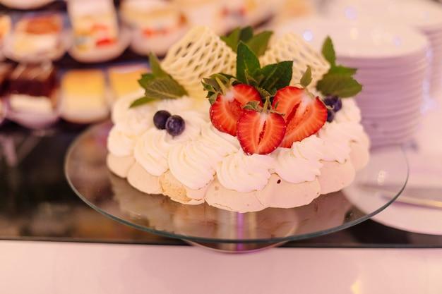 Magnífico bolo branco festivo decorado com morangos com hortelã e chocolate branco