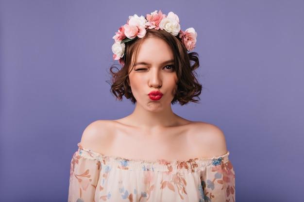 Magnífico modelo feminino branco com flores em pé de cabelo. sensual garota de cabelos curtos posando com beijo de expressão facial.