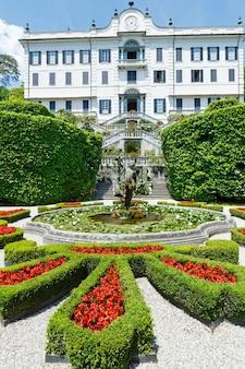 Magnífico parque com fonte, estátua, canteiros de flores. villa carlotta, itália, tremezzo, lago de como. construído em 1690.
