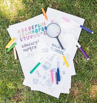 Magnifier em desenhos infantis na grama verde com marcadores
