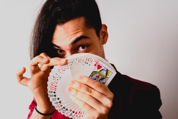 Mago fazendo truques com um baralho de cartas.