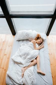 Magro descalça bonita jovem deitada na cama branca com cobertor e travesseiros e dormir. manhã relaxe no sofá. gengibre mulher descansando em apartamento de estúdio com piso de madeira e janelas enormes